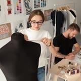 Il gruppo creativo degli stilisti che lavora in vestiti progetta lo studio immagine stock