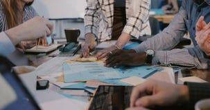 Il gruppo creativo multietnico che lavora al 'brainstorming' dietro la tavola, macchina fotografica inclina su sulla giovane donn archivi video