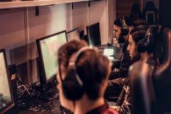 Il gruppo dei gamers adolescenti gioca in un video gioco con diversi giocatori sul pc in un club di gioco immagine stock libera da diritti