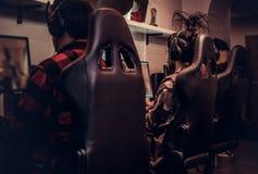 Il gruppo dei gamers adolescenti gioca in un video gioco con diversi giocatori sul pc in un club di gioco fotografia stock