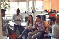 Il gruppo dei giovani in ufficio moderno ha la riunione e 'brainstorming' del gruppo mentre lavora al computer portatile ed al ca fotografia stock libera da diritti