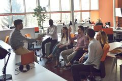 Il gruppo dei giovani in ufficio moderno ha la riunione e 'brainstorming' del gruppo mentre lavora al computer portatile ed al ca fotografia stock