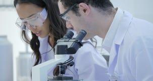 Il gruppo dei ricercatori di ricerca medica lavora al laboratorio moderno con gli scienziati che eseguono gli esperimenti, lavora stock footage