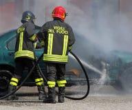Il gruppo dei vigili del fuoco italiani ha estinto il fuoco dell'automobile Immagini Stock Libere da Diritti