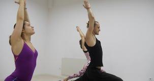 Il gruppo della classe di yoga che esercita lo stile di vita sano nel guerriero di yoga dello studio di forma fisica posa video d archivio