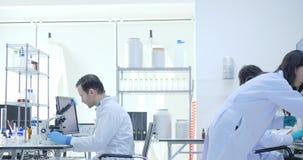 Il gruppo della WS dei ricercatori di ricerca medica lavora al laboratorio moderno con gli scienziati che eseguono gli esperiment stock footage