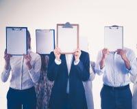 Il gruppo delle persone di affari che giudicano cartelle si avvicina al fronte su fondo bianco businesspeople Fotografia Stock Libera da Diritti
