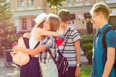 Il gruppo di adolescenti felici 13, 14 anni camminante lungo la via della città, amici si accoglie ad una riunione Immagini Stock Libere da Diritti