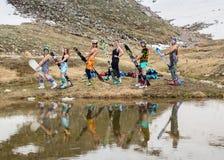 Il gruppo di adolescenti ha messo sulla neve nell'orario invernale Immagine Stock Libera da Diritti