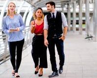 Il gruppo di affari con un uomo e due donne stanno camminando ed inoltre discutono circa il loro lavoro durante il tempo del gior immagini stock libere da diritti