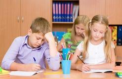 Il gruppo di allievi della scuola elementare prende la prova nella classe Immagini Stock