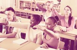 Il gruppo di allievi felici della scuola solleva le loro mani su Fotografia Stock