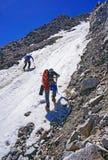 Il gruppo di alpinisti fa l'ascesa della montagna sul pendio di collina innevato tracciare Fotografie Stock