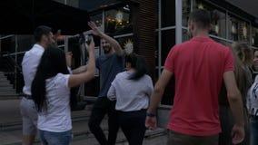 Il gruppo di amici che si incontrano davanti al club ed entra nel partito che va in giro insieme divertiresi stock footage