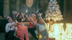 Il gruppo di amici di risata felici che sollevano le mani si avvicina all'albero di Natale Partito di celebrazione di Natale stock footage