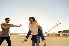 Il gruppo di amici si diverte sulla costruzione del tetto al tramonto immagini stock