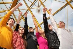 Il gruppo di amici si leva in piedi con i pugni alzati Immagini Stock