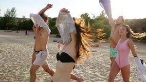 Il gruppo di amici si spoglia imbattersi nell'acqua di mare sul tramonto e getta le camice sulla spiaggia Gente felice allegra video d archivio