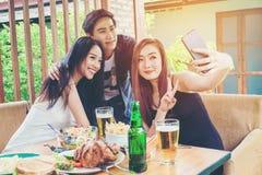 Il gruppo di amici sta prendendo il selfie e mangiando l'alimento sia enj felice fotografia stock