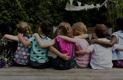 Il gruppo di asilo scherza il braccio degli amici intorno alla seduta insieme immagini stock