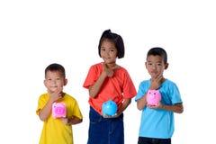 Il gruppo di bambini asiatici si diverte con il porcellino salvadanaio isolato su fondo bianco fotografie stock libere da diritti