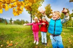Il gruppo di bambini che giocano con il giallo lascia in parco Immagine Stock