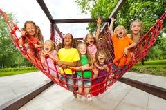 Il gruppo di bambini che si siedono sulla rete del campo da giuoco ropes Fotografie Stock Libere da Diritti