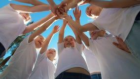 Il gruppo di bambini esegue il saluto motivazionale di sport con le mani sul campo da giuoco di calcio dell'iarda al giorno soleg video d archivio