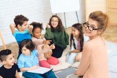 Il gruppo di bambini gioca un quiz con l'insegnante in blusa della pesca mentre nella classe di scuola primaria Fotografia Stock Libera da Diritti
