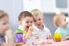 Il gruppo di bambini ha un pranzo nell'asilo fotografia stock libera da diritti