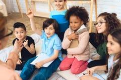 Il gruppo di bambini sta tirando le mani nella domanda del ` s dell'insegnante di risposta a scuola primaria Fotografie Stock