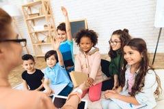 Il gruppo di bambini sta tirando le mani nella domanda del ` s dell'insegnante di risposta a scuola primaria Fotografia Stock