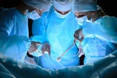 Il gruppo di chirurghi sul lavoro nella sala operatoria ha tonificato in blu Immagini Stock