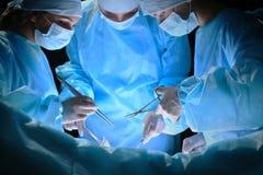 Il gruppo di chirurghi sul lavoro nella sala operatoria ha tonificato in blu Fotografie Stock Libere da Diritti