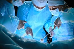Il gruppo di chirurghi sul lavoro nella sala operatoria ha tonificato in blu Fotografia Stock