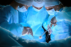 Il gruppo di chirurghi sul lavoro nella sala operatoria ha tonificato in blu Fotografia Stock Libera da Diritti