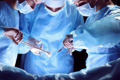 Il gruppo di chirurghi sul lavoro nella sala operatoria ha tonificato in blu Immagini Stock Libere da Diritti