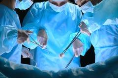 Il gruppo di chirurghi sul lavoro nella sala operatoria ha tonificato in blu Immagine Stock