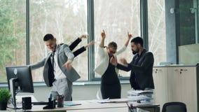 Il gruppo di colleghi allegri sta ballando nell'ufficio che celebrano l'evento della società al partito, carte di lancio, ridenti stock footage