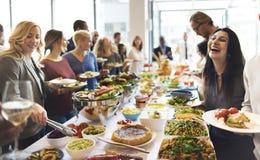 Il gruppo di diversa gente sta pranzando insieme fotografie stock libere da diritti