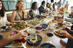 Il gruppo di diversa gente sta pranzando insieme fotografia stock