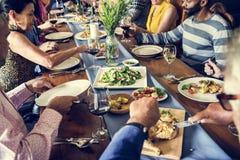 Il gruppo di diversi amici sta avendo una cena insieme fotografia stock