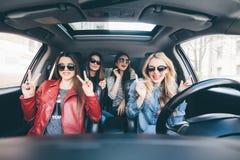 Il gruppo di divertiresi degli amici tenta l'azionamento l'automobile Cantando e ridere sulla strada fotografie stock