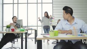 Il gruppo di donne creative asiatiche felici allegre di affari e gli uomini godono di e divertendosi ballare mentre lavorano nel  archivi video