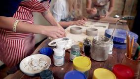 Il gruppo di donne sta lavorando nell'officina delle terraglie, facendo le tazze dell'argilla e la pittura video d archivio