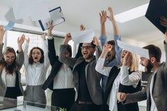 Il gruppo di gente di affari che celebra gettando le loro carte d'ufficio ed i documenti volano in aria, potere della cooperazion immagine stock