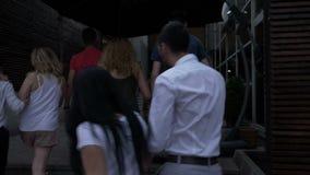 Il gruppo di gente allegra che cammina sulla via che cerca un club ed entra per fare festa archivi video