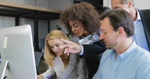 Il gruppo di gente di affari che analizza i documenti indica il dito sul motinor del computer, processo di lavoro del gruppo dell archivi video