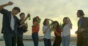 Il gruppo di giovani amici che ballano e che si divertono celebra con pane tostato ed il tintinnio che alzano i vetri al partito  stock footage