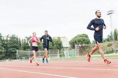Il gruppo di giovani che corrono sulla pista sistema Fotografia Stock Libera da Diritti